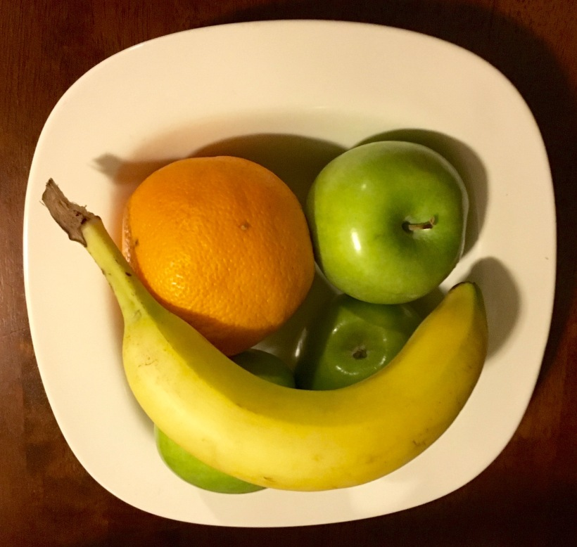 white bowl with banana, orange and green apples