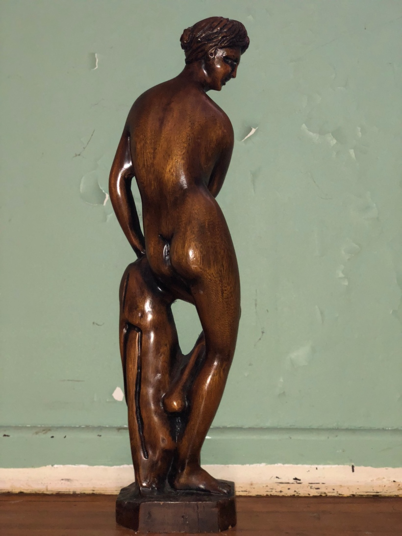 Wooden Lady facing the wall